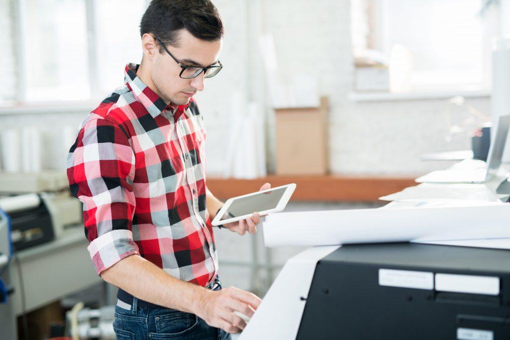 Afbeelding van een werknemer die een printer gebruikt op het werk